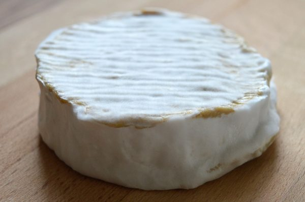 A Camembert-style vegan cheese presented on a wooden board